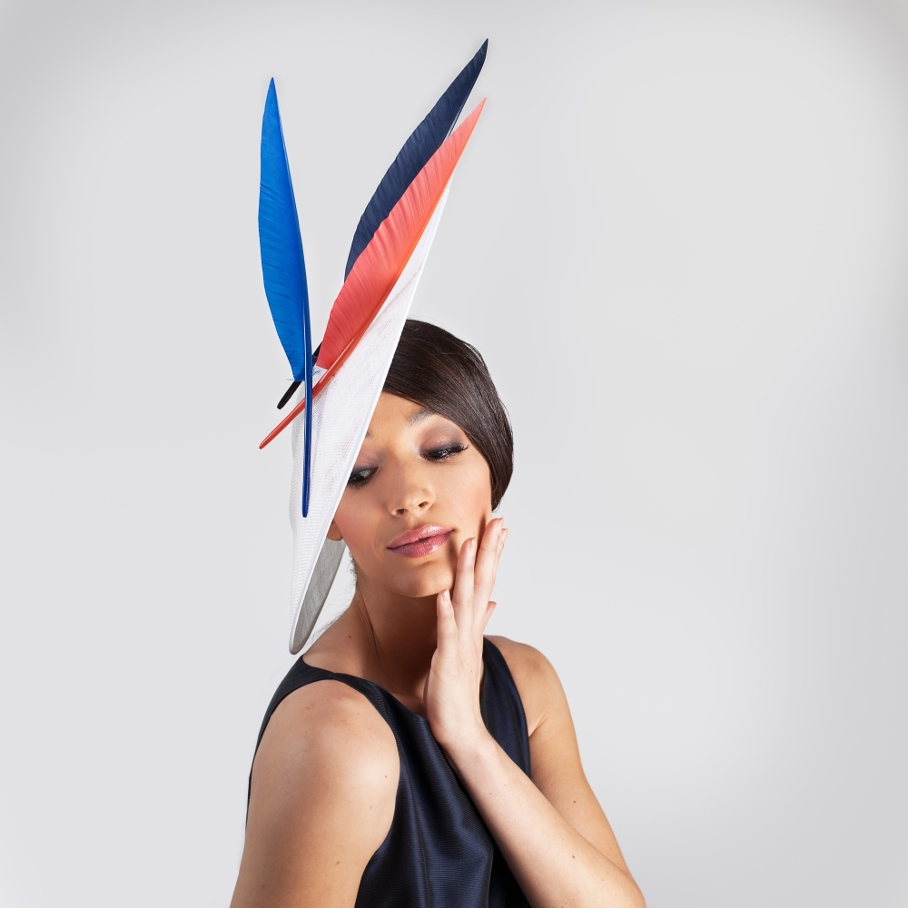 White disc hat with navy, royal blue and orange feathers